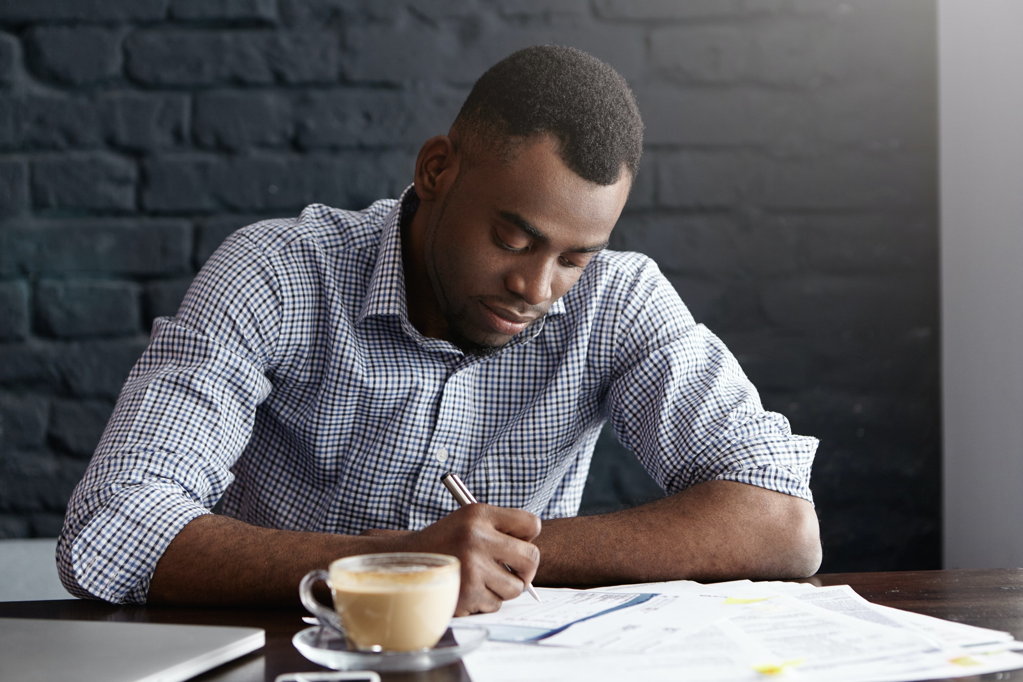 Hardworking young African office worker handwriting, filling in papers while doing accounting, revie